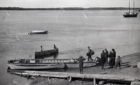 Men loading and boarding a barge