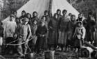Young Cree women, boys and girls in front of tent