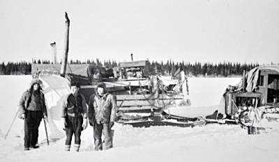 non-Cree men stand in front of a tractor sled train