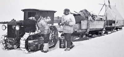 Men refuelling a tractor sled train on frozen land
